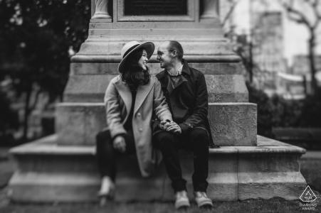London Couple se sentó en el banco mientras posaba para sus fotos de compromiso.