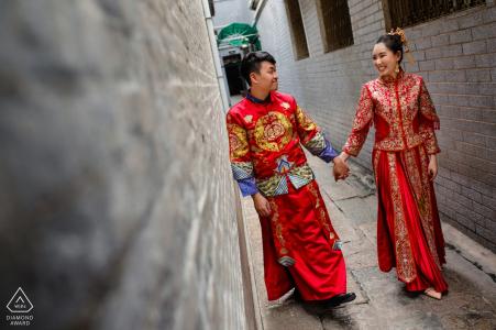 Pareja de la ciudad de Ho Chi Minh Caminando y riendo juntos para las fotos previas a la boda en atuendo rojo.