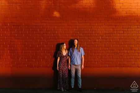 Pareja posa delante de una pared roja al atardecer en DTLA - Fotografía de compromiso en el centro de Los Ángeles, CA