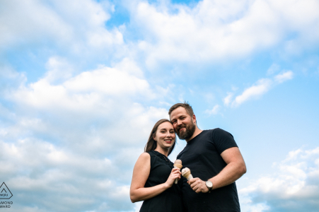 Perth, Ontario engagement session - Couple eats an ice cream under the blue sky and clouds.