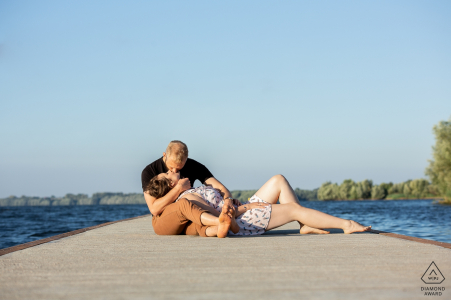 Jeziorsko Lake, Poland Engagement Photo Session - Image contains: Two young people are lying on the bridge.