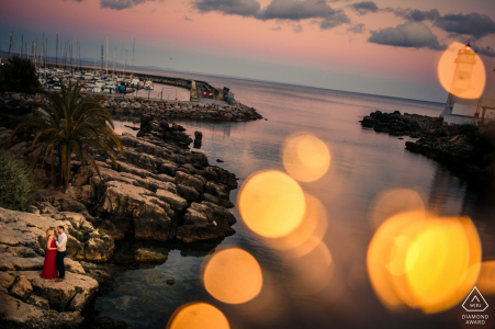 Cascais Lighthouse Session - Engagement Portrait of a Couple - Image contains:bokeh, rocks, water, beach, cove, red dress