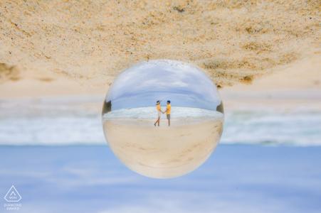 Retratos de compromiso previo a la boda en Phuket, Tailandia: vidrio, bola, esfera, playa, prisma, arena, pareja, agua, cielo