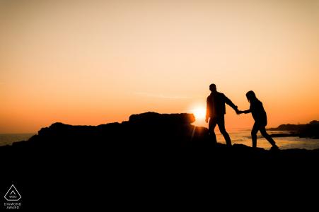 Photo silhouette d'un couple marchant sur des rochers sur une falaise au-dessus de l'océan au coucher du soleil | Photographe de fiançailles