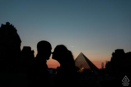 Foto de silueta de una pareja tocando cabezas durante la hora azul cerca del Louvre en París - Fotografía de compromiso