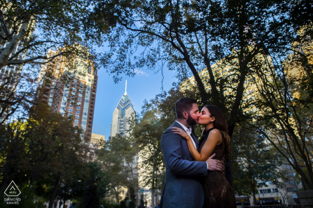 Engaged couple share a kiss at Rittenhouse Square in Philadelphia. PA Engagement Photography - Portrait contains: buildings, trees, park, trees, sky