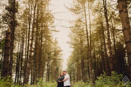 East Midlands, Reino Unido, sesión de retratos previos a la boda con una pareja posando en el bosque.