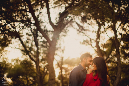 Derbyshire portrait photographer: Couple playing on pre-wedding shoot in the trees. Woman in Red.