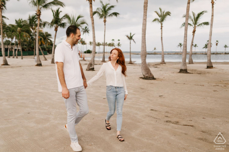 Portrait de fiançailles à Matheson Hammock Park, Miami, FL - Marcher dans le sable entre les arbres tout en se tenant la main.