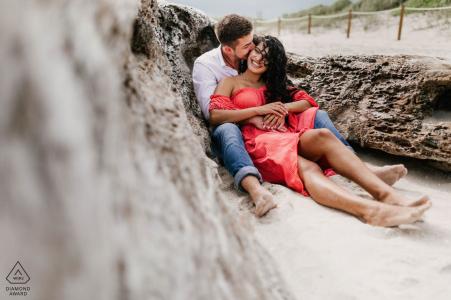 Portrait à South Pointe Park, South Beach, FL séance photo de fiançailles avec un couple assis dans le sable.