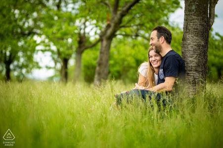 Brno compromiso sesión de fotos con una pareja sentada en el césped en el huerto de cerezos
