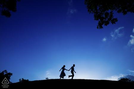 Retratos de compromiso previo a la boda de una pareja corriendo contra el cielo en Fujian, China