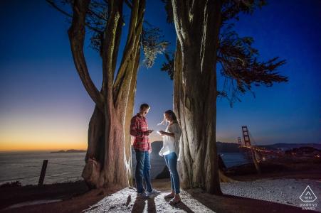 San Francisco, CA Couple sur leurs téléphones portables lors d'un tournage de fiançailles éclairé au coucher du soleil.