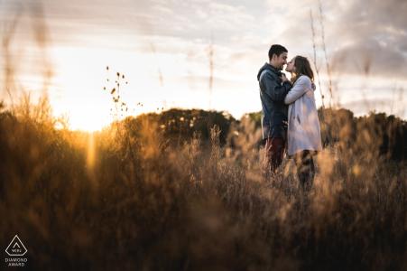 Agen, France portraits de fiançailles au coucher du soleil dans le domaine avec de hautes herbes