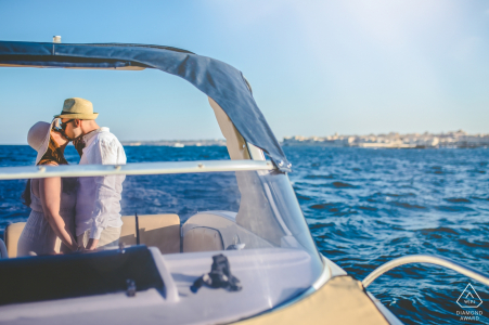 Siracusa summer loving couple engagement portraits on a boat on the open water