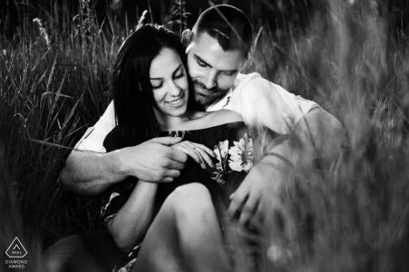 Sofia-Bulgaria Sesión de fotos previa a la boda con una pareja sentada en la hierba alta.