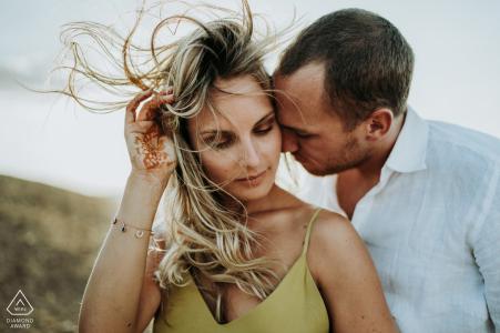 Un couple aux cheveux au vent lors de portraits de fiançailles dans le Désert d'Agafay