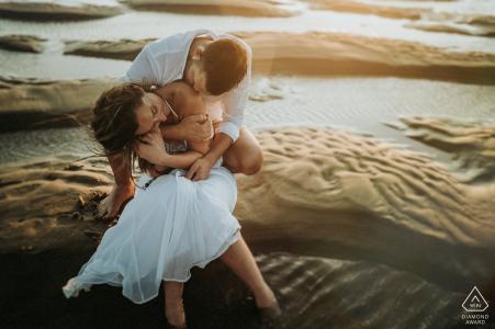 Couple fiancé couple assis sur la plage au coucher du soleil pour des portraits à Royan, Charente-maritime France