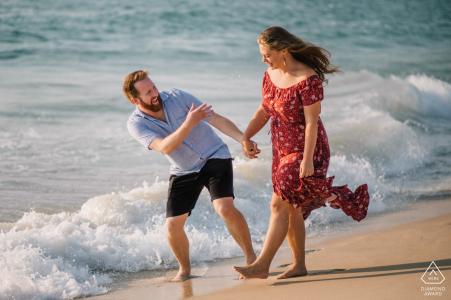 Perth pareja caminando y riendo juntos en la playa durante la sesión de retrato de compromiso.