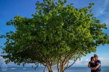 Couple à côté d'un arbre à Punta Mita lors d'une séance de photos d'engagement.