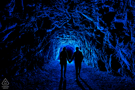 Bride and groom-to-be walking through dark tunnel in Canon City, Colorado.