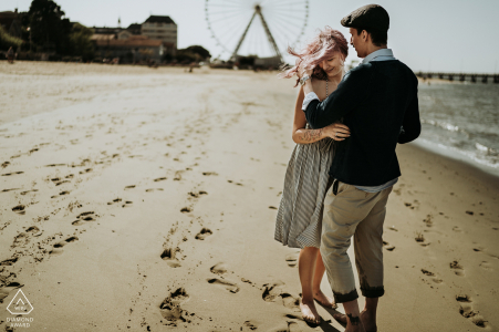 Séance engagement photo of an embraced couple at the beach.