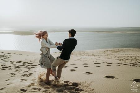 Imagen de compromiso Charente Marítimo - Pareja bailando y girando en la arena de la playa.
