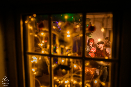 St. Martin's, Guernsey Engagement Shoot - Looking through window at couple with Christmas decorations