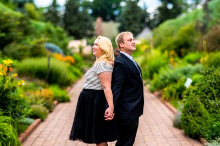 Photographie de fiançailles | Jardins botaniques de Denver, Denver, CO - Un couple engagé se tient dos à dos et admire les jardins - un panorama de Brenizer