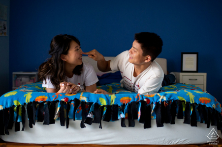 los angeles couple in bed with blue background - in-home engagement shoot