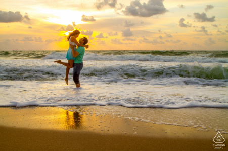 Séance de portraits à Fort Lauderdale Beach pour l'engagement - Il la soulève alors qu'ils profitent du lever du soleil sur la plage.