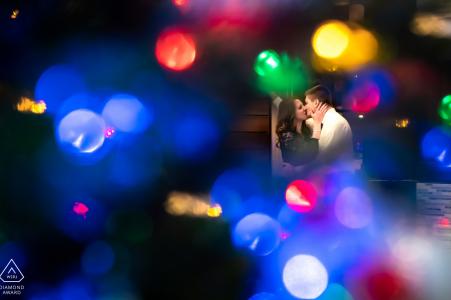 Fargo, Dakota du Nord Radisson photographie de fiançailles au centre-ville - Le couple s'embrasse derrière les lumières d'un arbre de Noël.