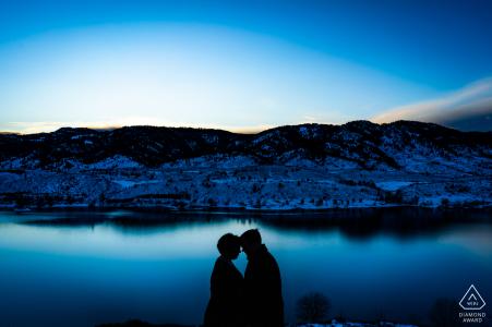 在科罗拉多州科林斯堡山麓的冬季订婚活动中,一对夫妻分享了一个亲密的时光,试图在日落时保持温暖。