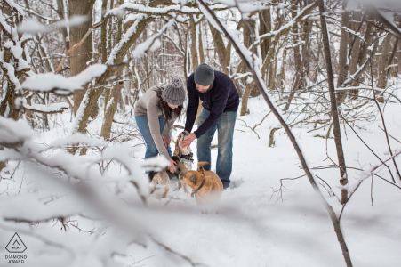 Engagement session in Guelph, Ontario, Canada of a couple walking through the snowy woods with their dogs