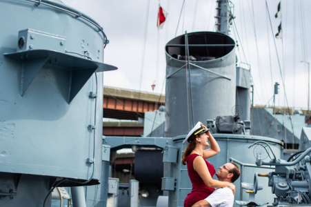 Albany, New York engagement portraits | The bride to be steal's her fiance's sailor's cap as he lifts her on board a WWII battleship.