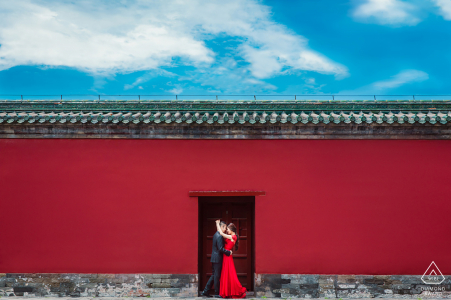 The couple stand by the ancient wall of the historical building in Temple of Heaven.