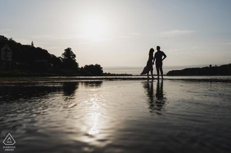 Parnay, Francia Siluetas de pareja comprometida durante el rodaje previo a la boda en las aguas de la playa