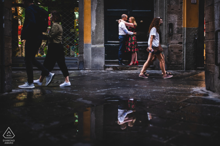 An engaged couple hold each other in a street scene with puddle reflections in the beautiful city of Lucca