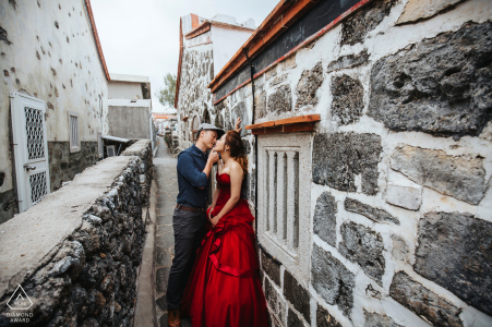 Penghu couple show affection to one another during their engagement photo shoot amongst a network of stone buildings