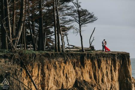Retrato de compromiso de Moss Beach, California, con un vestido rojo que fluye cerca de los acantilados
