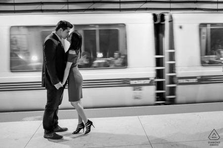 Beso en la plataforma Bart en San Francisco de una pareja durante una sesión de fotos de compromiso
