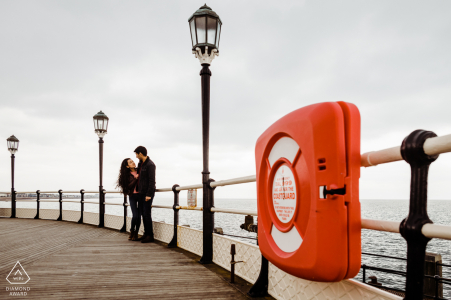Worthing Pier, West Sussex, UK | Couple embracing on Pier with lifebouy ring in foreground
