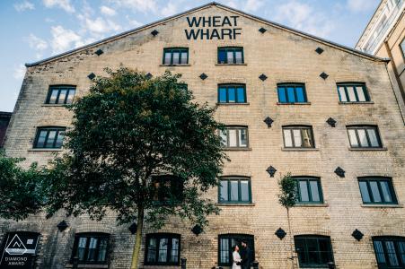 Shad Thames, Londres, Royaume-Uni   Un couple enlacé et encadré par un grand bâtiment historique, Wheat Wharf
