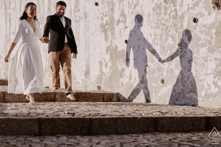 After her feet started hurting, the bride-to-be took her shoes off. Her fiancée decided to join her and so they walked with their bare feet in the streets of Óbidos.