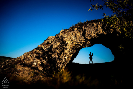 Silhouetted couple framed by a natural arch at Malhostovicka pecka
