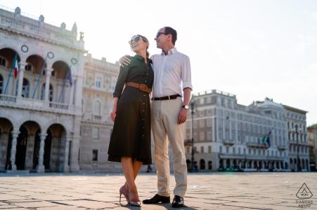 Pareja feliz en Piazza Unità d'Italia durante una sesión de compromiso en Trieste, Italia