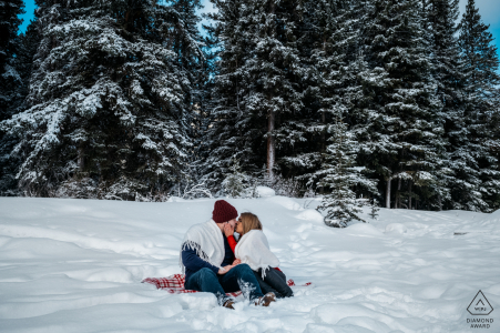 a young engaged couple are Cuddling under the blanket in the snow in Lake Minnewanka, AB, Canada