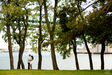 Boston, Massachusetts verlobte Paar unter Bäumen während ihrer Porträtsitzung am Wasser