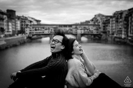 the couple is sitting back-to-back on the wall of the bridge while laughing over the waters of Santa Trinita bridge in Florence
