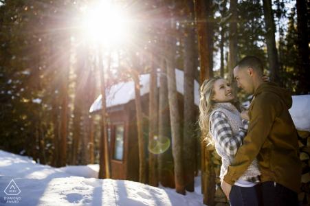 Le jeune couple s'embrasse alors que la lumière du soleil filtre à travers les arbres au réservoir Sawmill à Breckenridge pendant leur session de fiançailles d'hiver